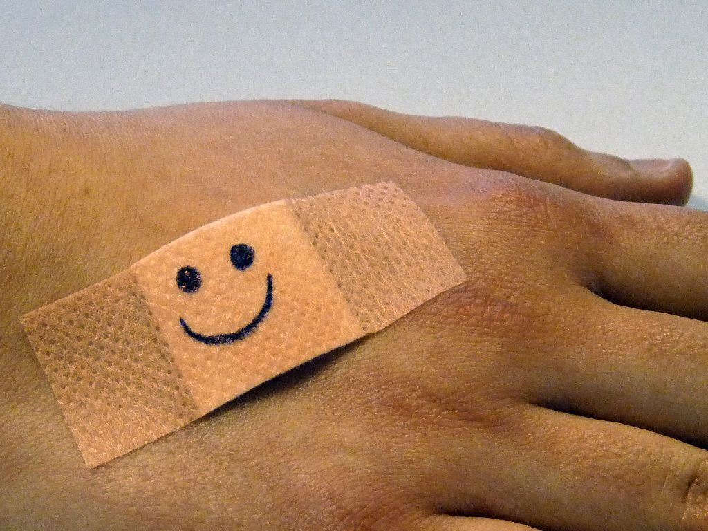Band aid with smiley on someone's hand
