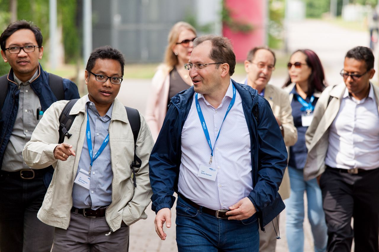 Several people with blue lanyards talking while walking